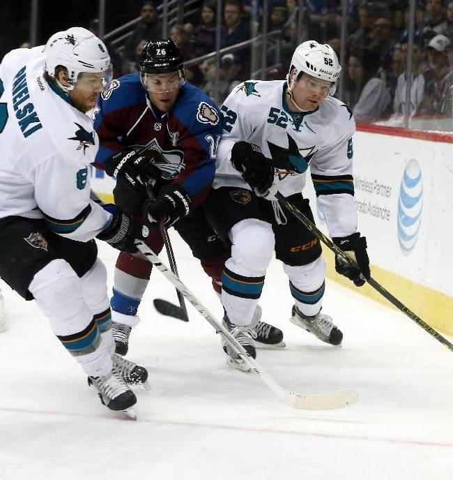 San Jose Sharks center Joe Pavelski, left, battles for control of puck with Colorado Avalanche center Paul Stastny, center, as Sharks defenseman Matt Irwin covers in the first period of an NHL hockey game on Saturday, March 29, 2014, in Denver