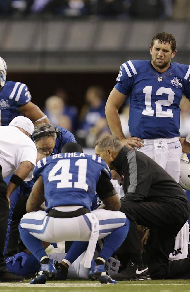 Indianapolis Colts players gather around as trainers talk to Indianapolis Colts wide receiver Reggie Wayne (87) after Wayne injures his knee during the second half of an NFL football game, Sunday, Oct. 20, 2013, in Indianapolis