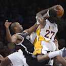 Los Angeles Lakers forward Jordan Hill, right, tries to put up a shot as Brooklyn Nets center Jason Collins blocks it during the first half of an NBA basketball, Sunday, Feb. 23, 2014, in Los Angeles The Associated Press