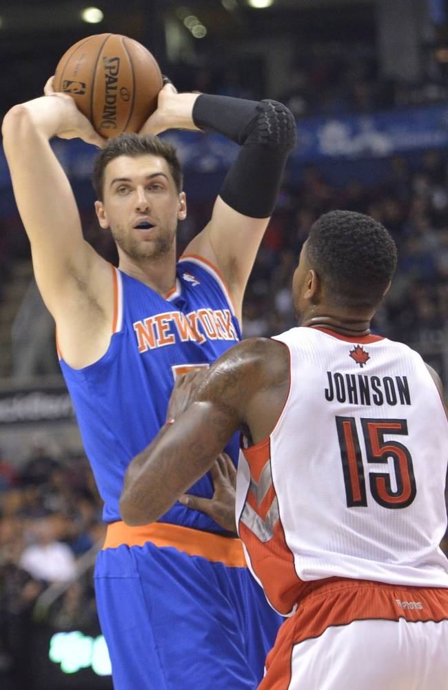 New York Knicks Andrea Bargnani passes the ball over Toronto Raptors Amir Johnson (15) during first half NBA pre-season basketball action in Toronto on Tuesday, Oct. 21, 2013