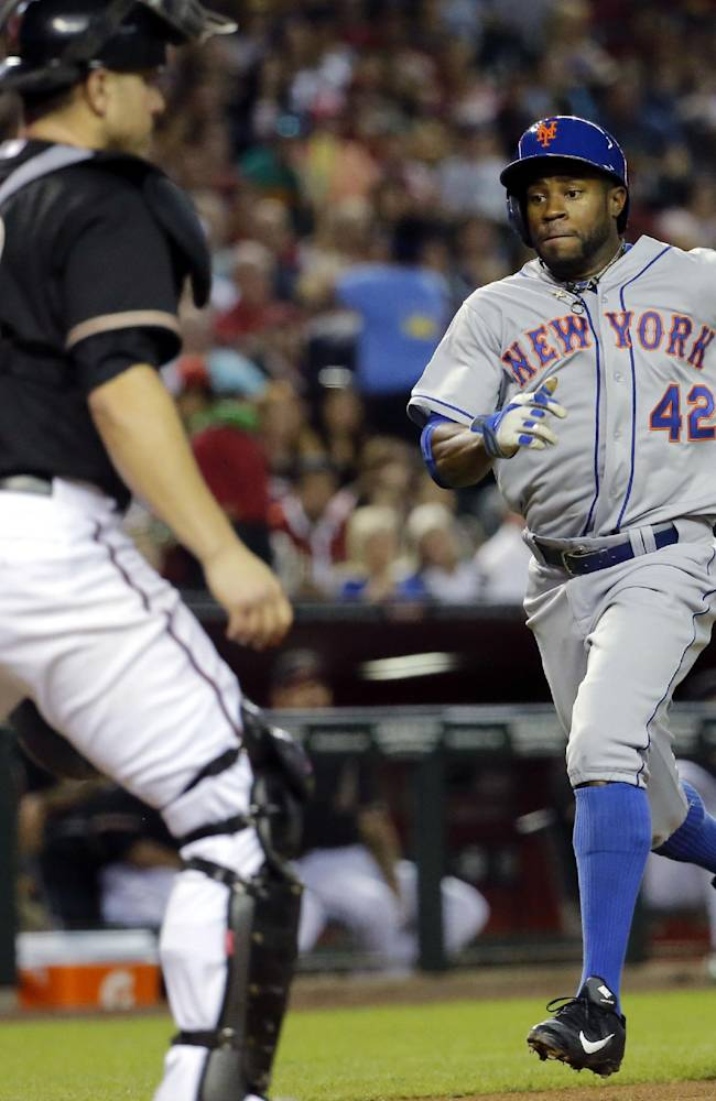 Arizona Diamondbacks catcher Miguel Montero, left, waits for the throw as New York Mets' Eric Young Jr. scores on a hit by teammate Daniel Murphy during the fourth inning of the MLB National League baseball game on Tuesday, April 15, 2014, in Phoenix