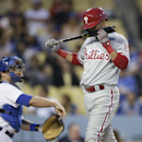 Philadelphia Phillies' Freddy Galvis checks his bat after swinging at a pitch, while Los Angeles Dodgers catcher Tim Federowicz throws the ball to starting pitcher Dan Haren during the second inning of a baseball game Thursday, April 24, 2014, in Los Ange