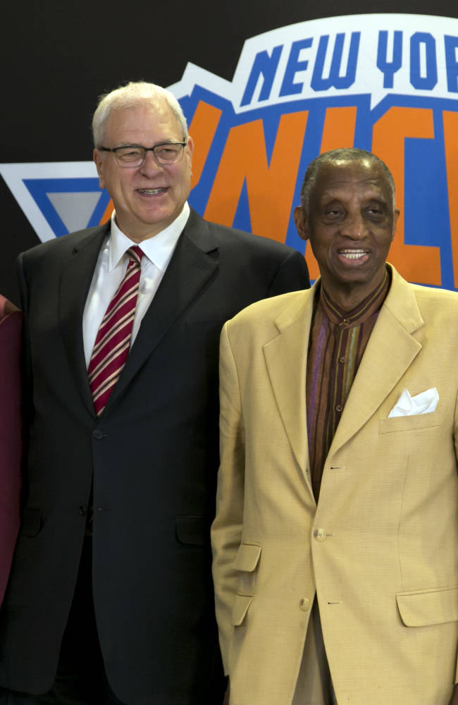 New York Knicks new team president Phil Jackson, center, poses for photos with former teammates Walt Frazier, left, and Dick Barnett, after a news conference where he was introduced, at New York's Madison Square Garden, Tuesday, March 18, 2014. Jackson signed a five-year contract that will reportedly pay him at least $12 million annually and said he will spend significant time in New York