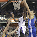 Sacramento Kings guard Isaiah Thomas, center, drives to the basket between Golden State Warriors' Klay Thompson, left, and Andrew Bogut, of Australia in the closing moments of an NBA basketball game in Sacramento, Calif., Sunday, Dec. 1, 2013. Thomas mis