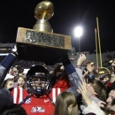 Mississippi tight end Jack Nuismer carries the Egg Bowl trophy through a sea of fans after Mississippi defeated No. 25 Mississippi State 41-24 in an NCAA college football game in Oxford, Miss., Saturday, Nov. 24, 2012. (AP Photo/Rogelio V. Solis)