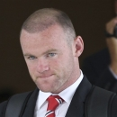 In this photo taken July 11, 2013, Wayne Rooney of England and Manchester United football club, walks to a waiting coach after arriving at Don Muang international airport in Bangkok, Thailand. Manchester United said on Thursday that striker Rooney is flying back to England from the club's preseason tour of Asia because of injury, a day after arriving in the Thai capital. United said that Rooney injured a hamstring in training. (AP Photo/Apichart Weerawong)