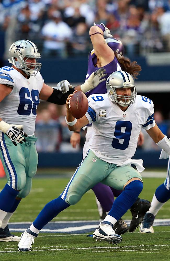 Dallas Cowboys quarterback Tony Romo (9) manage to run away from Minnesota Vikings defense for a first down during the second half of an NFL football game Sunday, Nov. 3, 2013, in Arlington, Texas