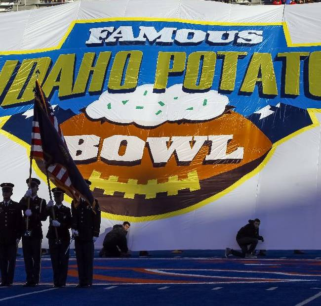 A large banner for the Famous Idaho Potato Bowl is raised behind the U.S. flag during the national anthem before the first half of an NCAA college football game between Buffalo and San Diego State in Boise, Idaho, on Saturday, Dec. 21, 2013