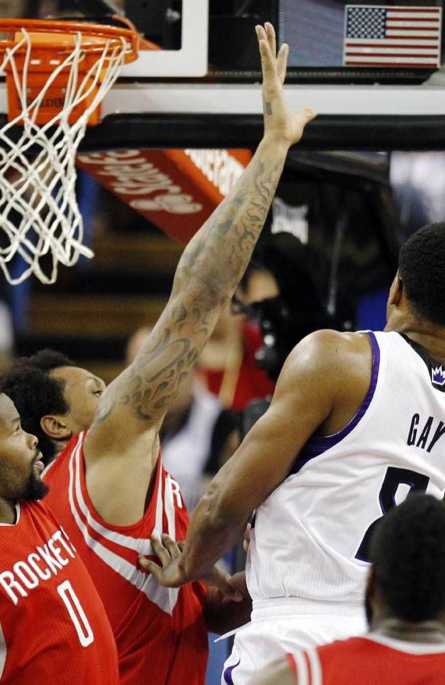 Sacramento Kings forward Rudy Gay (8) scores around Houston Rockets point guard Aaron Brooks (0) and Rockets forward Greg Smith, back left, during the first half of an NBA basketball game in Sacramento, Calif., Sunday, Dec. 15, 2013