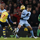 Arsenal's Alexis Sanchez, No 17, shoots at goal as Manchester City's Vincent Kompany, left and Manchester City's Martin Demichelis grimace as they avoid the ball during the English Premier League soccer match between Manchester City and Arsenal at the Eti