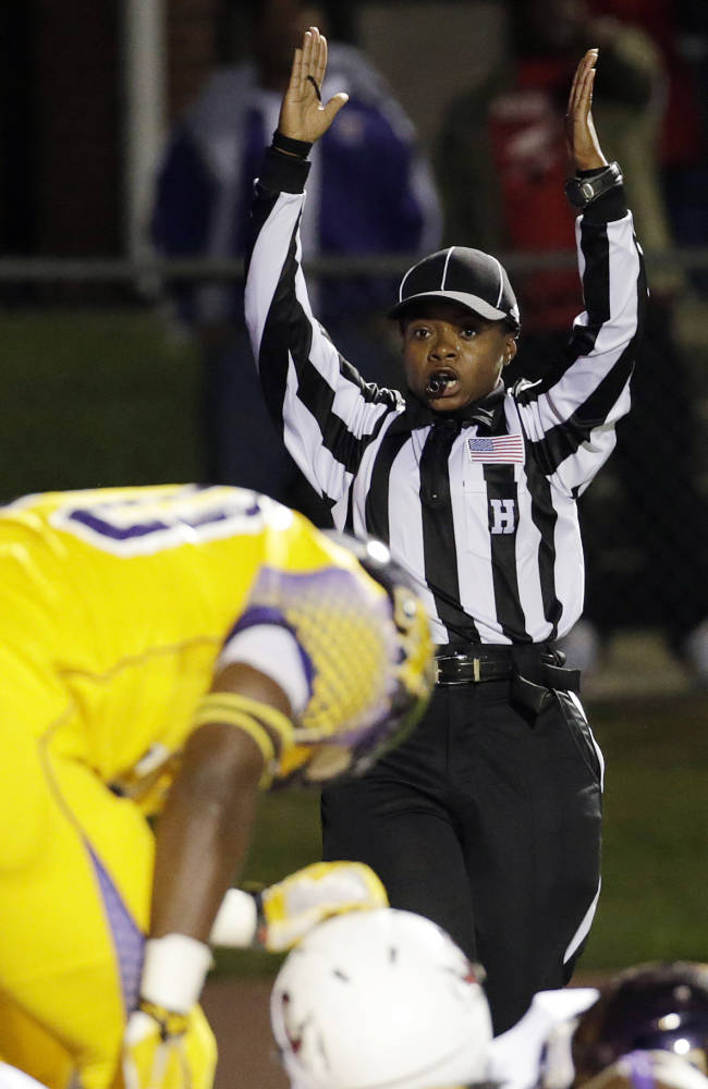 Referee Yvonda Lewis signals for a touchdown in the first half of an NCAA college football game between Miles College and Lane College in Fairfield, Ala., Thursday, Oct. 24, 2013