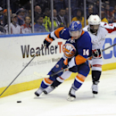 Washington Capitals right wing Joel Ward (42) overtakes New York Islanders' Thomas Hickey (14) in the third period of an NHL hockey game on Saturday, April 5, 2014, in Uniondale, N.Y. The Capitals won 4-3 in a shoot out The Associated Press