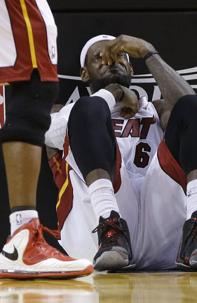 Miami Heat's LeBron James sits on the court after being elbowed by Charlotte Bobcats' Josh McRoberts during the second half in Game 2 of an opening-round NBA basketball playoff series, Wednesday, April 23, 2014, in Miami. The Heat defeated the Bobcats 101-97