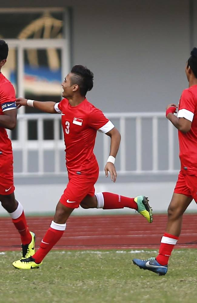 Singapore's Hariss Harun, left, celebrates with his teammates Mohamad Sahil Suhaimi, center, and Muhammad Fariz Ramli during a soccer match for third place against Malaysia during the 27th Southeast Asian Games in Naypyitaw, Myanmar, Saturday, Dec. 21, 2013