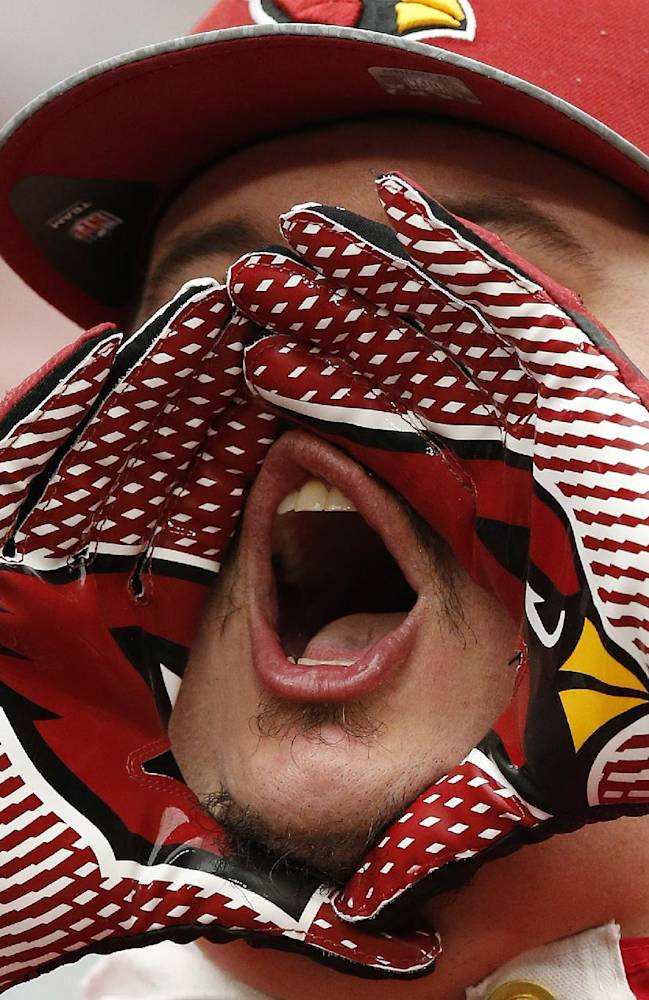 An Arizona Cardinals fan shouts encouragement during the first day of the NFL football teams' training camp, Saturday, July 26, 2014, in Glendale, Ariz