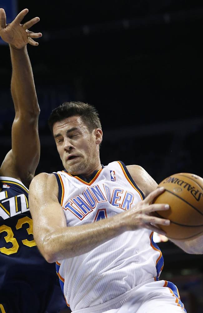 Oklahoma City Thunder forward Nick Collison (4) grabs a rebound in front of Utah Jazz forward Mike Harris (33) in the fourth quarter of a preseason NBA basketball game in Oklahoma City, Sunday, Oct. 20, 2013. Oklahoma City won 88-82