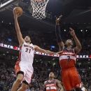 Toronto Raptors' Greivis Vasquez, left, scores on Washington Wizards' John Wall, right, as Wizards' Bradley Beal, center, looks on during second half NBA basketball action in Toronto, Thursday, Feb. 27, 2014 The Associated Press