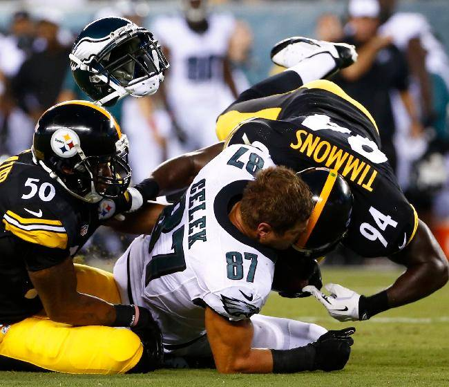 Philadelphia Eagles' Brent Celek, center, is hit by Pittsburgh Steelers' Ryan Shazier, left, and Lawrence Timmons during the first half of an NFL preseason football game, Thursday, Aug. 21, 2014, in Philadelphia