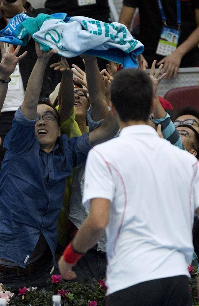 Spectators try to grab a towel thrown by Novak Djokovic of Serbia after he defeated Lukas Rosol of the Czech Republic in the China Open tennis tournament at the National Tennis Stadium in Beijing, China Tuesday, Oct. 1, 2013