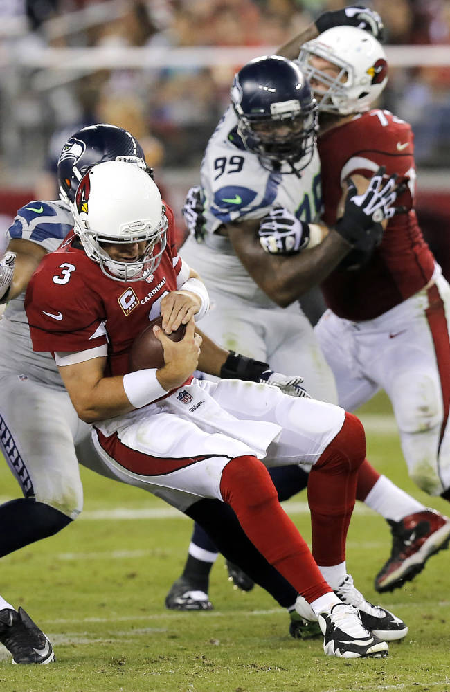 Arizona Cardinals quarterback Carson Palmer (3) is tackled by Seattle Seahawks outside linebacker K.J. Wright, left, as Seahawks defensive tackle Tony McDaniel (99) is slowed by Cardinals tackle Eric Winston (73) during the second half of an NFL football game, Thursday, Oct. 17, 2013, in Glendale, Ariz