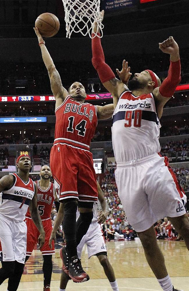Washington Wizards forward Drew Gooden (90) reaches to block a shot by Chicago Bulls guard D.J. Augustin (14) at the basket during the first half of Game 4 of an opening-round NBA basketball playoff series in Washington, Sunday, April 27, 2014