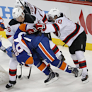 New York Islanders center Mikhail Grabovski (84) is knocked off his feet by New Jersey Devils Seth Helgeson (45) and Peter Harrold (10) in the third period of a preseason NHL hockey game Friday, Sept. 26, 2014, in New York. The Islanders won 3-2 in a sho