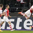 Arsenal's Lukas Podolski, right celebrates scoring the winning goal as teammate Arsenal's Alexis Sanchez leaps onto his back during the Group D Champions League match between Anderlecht and Arsenal at Constant Vanden Stock Stadium in Brussels, Belgium, We