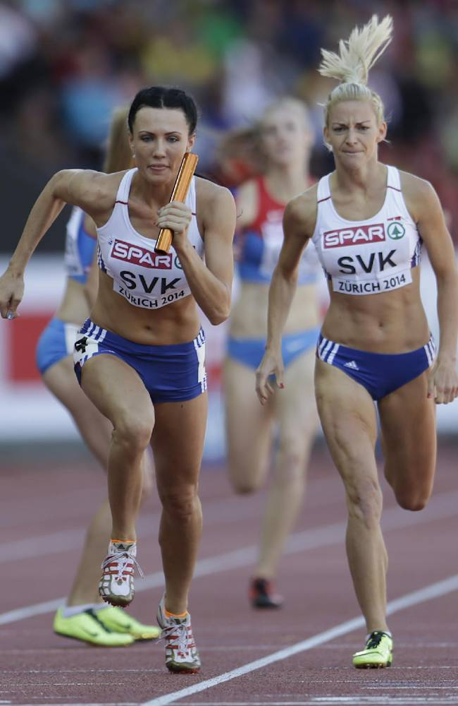 Slovakia's Andrea Holleyova, right, has handed over the baton to Iveta Putalova in a 4x400m relay heat during the European Athletics Championships in Zurich, Switzerland, Saturday, Aug. 16, 2014