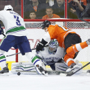 Philadelphia Flyers left wing R.J. Umberger, top right, goes over Vancouver Canucks goalie Ryan Miller, bottom right, as defenseman Kevin Bieksa looks to clear the puck away during the first period of an NHL hockey game, Thursday, Jan. 15, 2015, in Philad