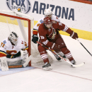 Arizona Coyotes' Shane Doan (19) works the puck in on Calgary Flames goaltender Karri Ramo (31), of Finland, as Calgary's Kris Russell (4) defends during the first period of an NHL game Saturday, Nov. 29, 2014 in Glendale, Ariz The Associated Press