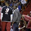 Miami Heat's Dwyane Wade, right, stands with Rashard Lewis (9) during a time out during the first half of an NBA basketball game against the Detroit Pistons, Tuesday, Dec. 3, 2013, in Miami. Wade did not play due to soreness in his knees. (AP Photo/Lynne Sladky)