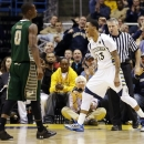Marquette's Vander Blue (13) reacts after scoring in front of South Florida's Martino Brock (0) during the second half of an NCAA college basketball game, Monday, Jan. 28, 2013, in Milwaukee. Blue scored 30 points as Marquette won 63-50. (AP Photo/Jeffrey Phelps)