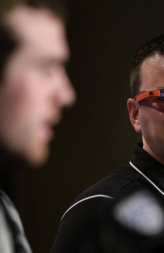 Stanford offensive coordinator Mike Bloomgren, right, wears Google Glass while listening to quarterback Kevin Hogan during a news conference on Friday, Dec. 27, 2013, in Los Angeles. Stanford is scheduled to play Michigan State in the Rose Bowl NCAA college football game in Pasadena, Calif., on New Year's Day