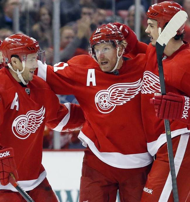 Detroit Red Wings' Daniel Alfredsson (11) celebrates his assist with teammates Pavel Datsyuk (13), of Russia, and Jonathan Ericsson (52), of Sweden, on a goal by Joakim Andersson during the second period of an NHL hockey game against the Calgary Flames, Thursday, Dec. 19, 2013, in Detroit