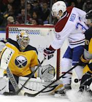 Buffalo Sabres goaltender Ryan Miller, left, makes a save off the stick of Montreal Canadiens left winger Travis Moen (32) as Sabres defenseman Christian Ehrhoff, of Germany, closes in during the second period of an NHL hockey game in Buffalo, N.Y., Wednesday, Nov. 27, 2013. (AP Photo/Gary Wiepert)