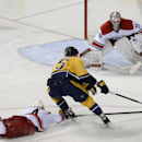 Carolina Hurricanes defenseman Andrej Sekera (4), of Czech Republic, dives on the ice attempting to stop Nashville Predators left wing Viktor Stalberg (25), of Sweden, from scoring in the third period of an NHL hockey game Tuesday, Jan. 6, 2015, in Nashvi
