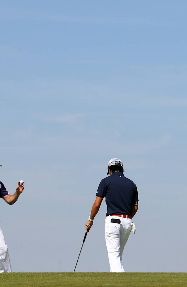 Lee Westwood of England holds up his ball after putting out as Ryo Ishikawa of Japan prepares to putt on the 6th green during the first day of the British Open Golf championship at the Royal Liverpool golf club, Hoylake, England, Thursday July 17, 2014