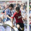 Manchester United's Shinji Kagawa, right, is tackled by West Bromwich Albion's Claudio Yacob during their English Premier League soccer match at The Hawthorns Stadium, West Bromwich, England, Sunday May. 19, 2013. (AP Photo/Jon Super)