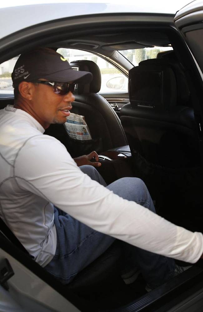 Golfer Tiger Woods, gets into a car after arriving at the Indira Gandhi International airport, in New Delhi, India, Monday, Feb. 3, 2014. Woods arrived Monday on his first visit to India to play an exhibition with a top business executive. (AP Photo /Manish Swarup)