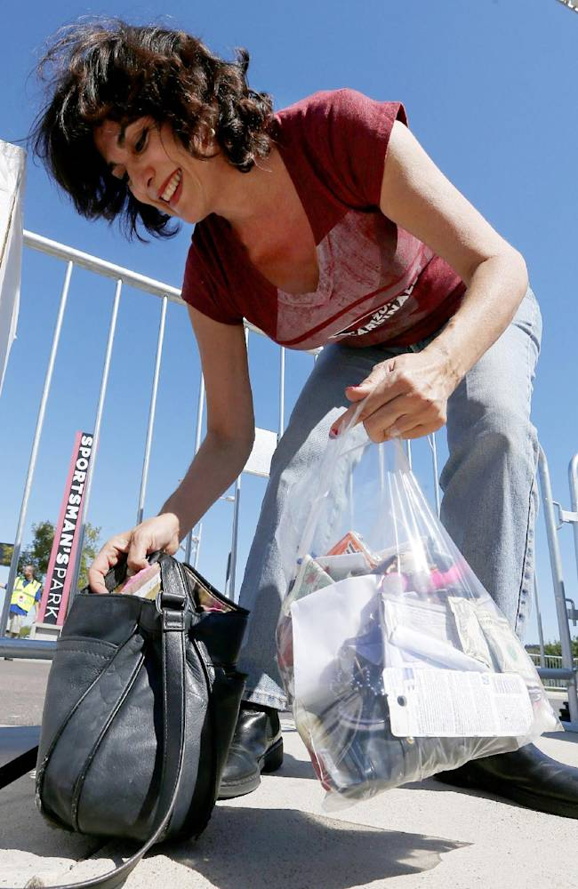 Arizona Cardinals fan Elizabeth Saliba, of Phoenix, tries to move all of her belongings from her purse into an NFL approved clear bag before entering the stadium prior to an NFL football game on Sunday, Sept. 15, 2013, in Glendale, Ariz