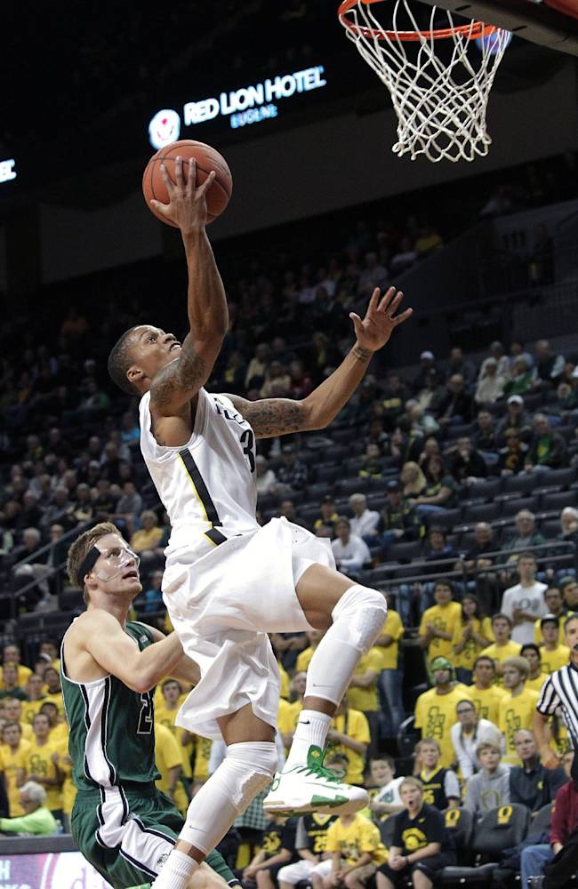 Oregon guard Joseph Young, right, scores against Utah Valley forward Zach Nelson during the first half of an NCAA college basketball game in Eugene, Ore., Tuesday, Nov. 19, 2013