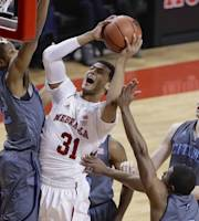 Nebraska's Shavon Shields (31) goes for a layup against The Citadel's Brian White, left, Marshall Harris III, bottom right, and Tom Koopman, right, during the first half of an NCAA college basketball game in Lincoln, Neb., Saturday, Dec. 21, 2013. (AP Photo/Nati Harnik)