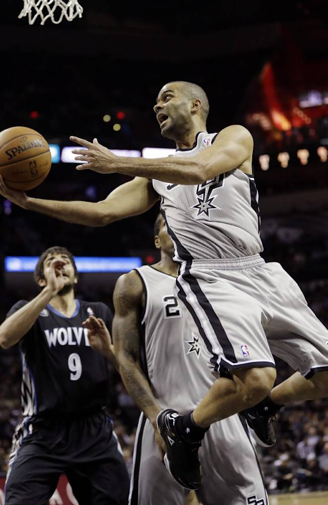 San Antonio Spurs' Tony Parker (9), of France, tries to score as Minnesota Timberwolves' Ricky Rubio (9) looks on during the first half on an NBA basketball game, Sunday, Jan. 12, 2014, in San Antonio