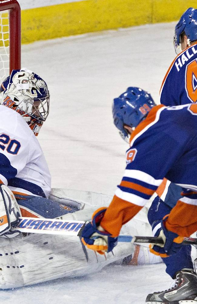 New York Islanders goalie Evgeni Nabokov (20) lets the puck past him on a shot from Edmonton Oilers' Sam Gagner (89) as Ryan Strome (18) and Taylor Hall (4) chase during overtime NHL hockey action in Edmonton, Alberta, on Thursday March 6, 2014