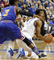 Kentucky's Andrew Harrison, right, looks for a teammate while under pressure from Texas-Arlington's Jamel Outler (3) during the first half of an NCAA college basketball game, Tuesday, Nov. 19, 2013, in Lexington, Ky. (AP Photo/James Crisp)