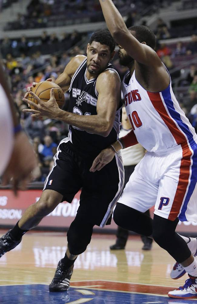San Antonio Spurs forward Tim Duncan (21) drives on Detroit Pistons forward Greg Monroe (10) during the first half of an NBA basketball game in Auburn Hills, Mich., Monday, Feb. 10, 2014