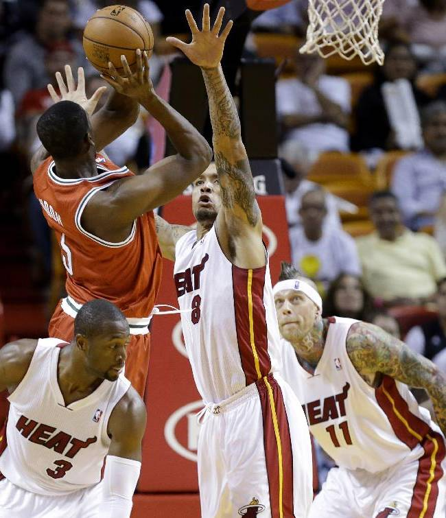 Milwaukee Bucks' Ekpe Udoh, left, is fouled by Miami Heat's Michael Beasley (8) while Heat's Dwyane Wade (3) and Chris Andersen (11) defend during the first half of an NBA basketball game Tuesday, Nov. 12, 2013, in Miami