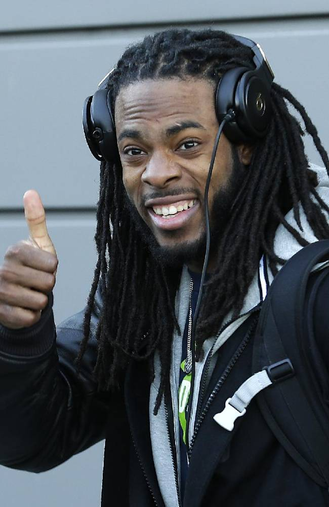 Seattle Seahawks cornerback Richard Sherman gives a thumbs-up as he leaves team's headquarters, Sunday, Jan. 26, 2014, in Renton, Wash., to board a bus for his flight to play the Denver Broncos in the NFL Super Bowl XLVIII football game in East Rutherford, N.J