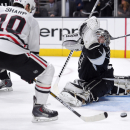 Los Angeles Kings goalie Jonathan Quick, right, deflects a shot as Chicago Blackhawks left wing Patrick Sharp tries to get a stick on it during the third period of an NHL hockey game, Wednesday, Jan. 28, 2015, in Los Angeles. The Kings won 4-3 The Associ