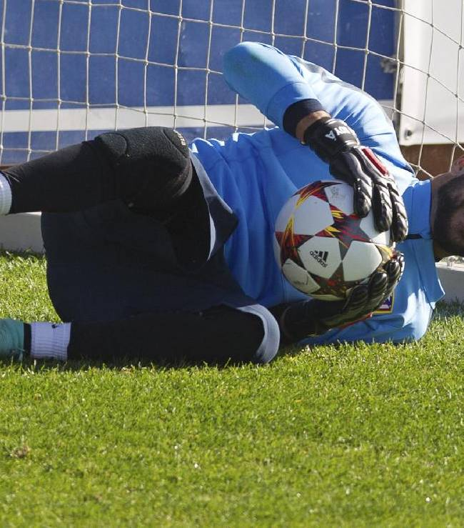 Atletico's goalkeeper Miguel Angel Moya makes a save during a training session in Madrid, Spain, Tuesday, Oct. 21, 2014. Atletico de Madrid will play Malmo Wednesday in a Group A Champions League match